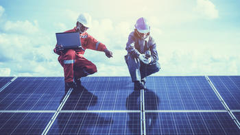 Two workers with hard hats crouching on solar panels