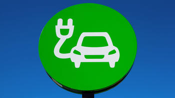 Green sign of drawn car with electric plug on blue background